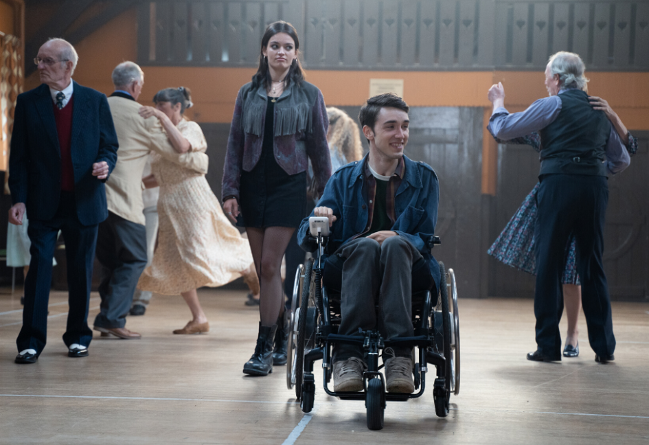 A still from Sex Education - showing Isaac and the female lead in a church hall surrounded by older couples dancing.