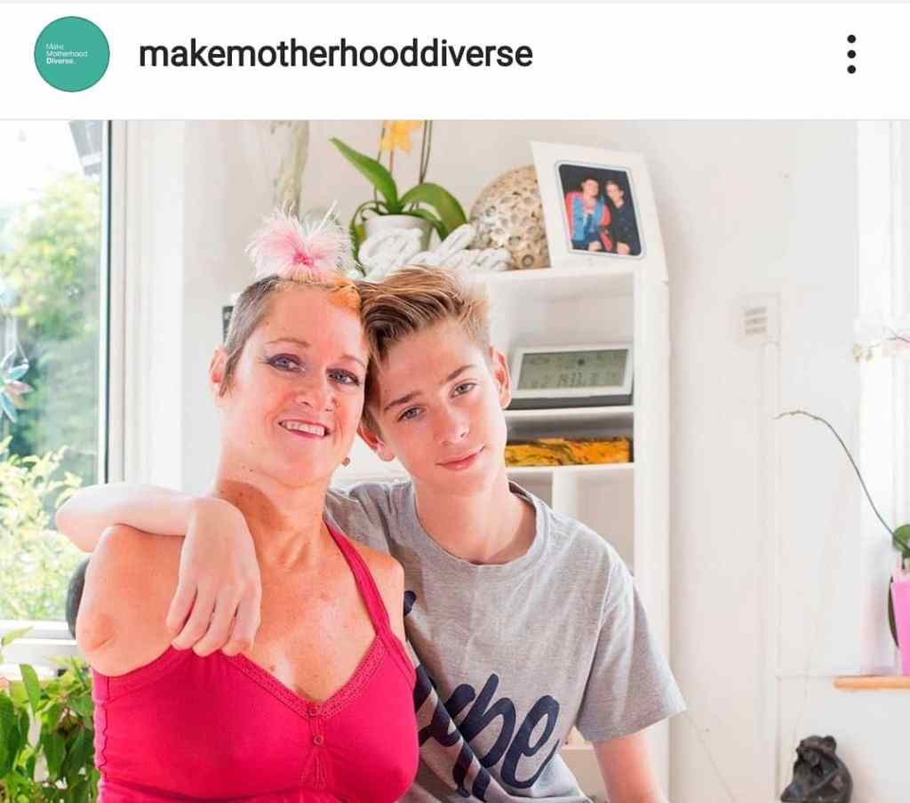A photo of Alison Lapper, a disabled white woman with very short hair and no arms, wearing a hot pink top and smiling. Her son - a white teenager with blonde hair - has his arm round her shoulder.