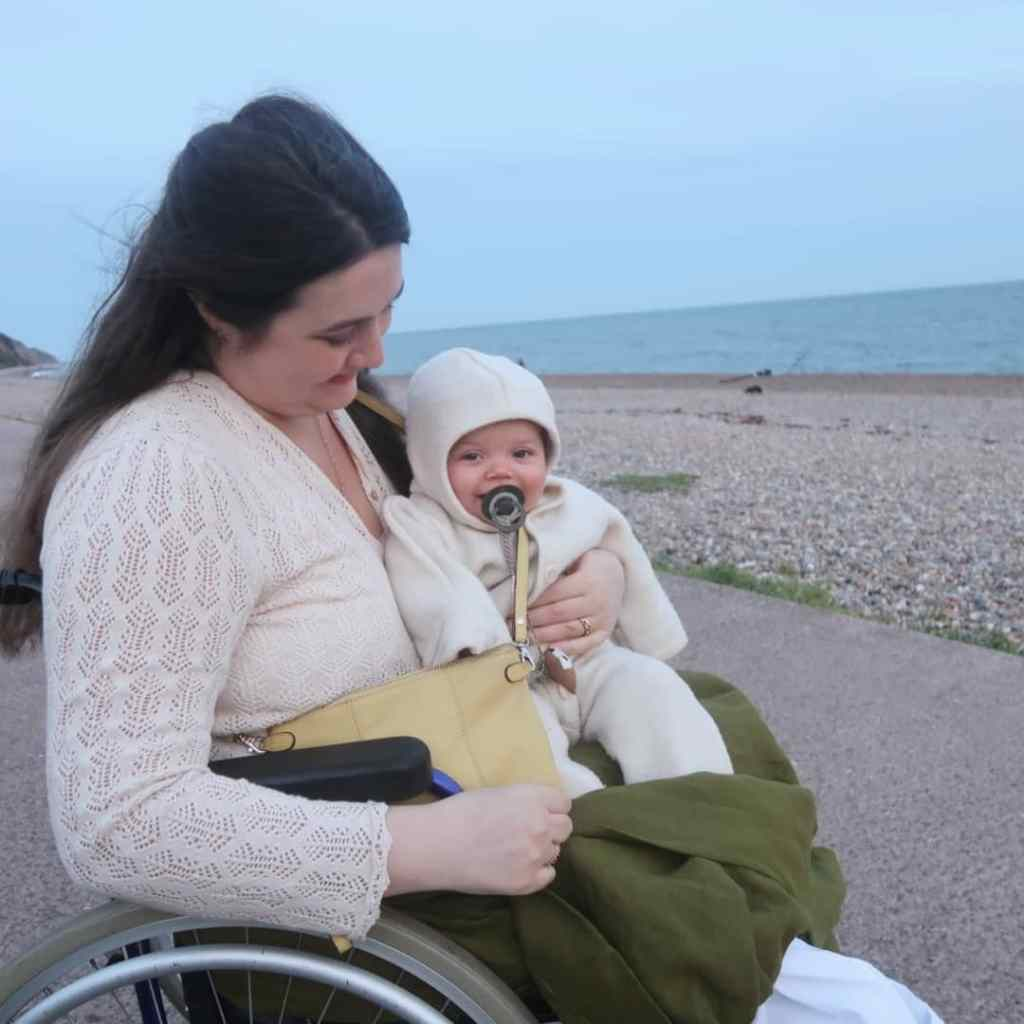 Lucy - a white woman with long brown hair - is sitting in her wheelchair on a beach. Windswept, would be a word. Her young baby Viola is sitting on her lap in a wool all-in-one, smiling at the camera. Lucy's green linen skirt is pulled up around Viola's feet to keep them warm.