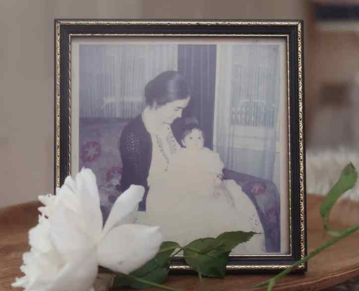 A framed photo of a young woman with dark hair and pale skin holding a very alert baby in a traditional christening dress. It does look a bit Edwardian. There's a rose lying in front of the photo.