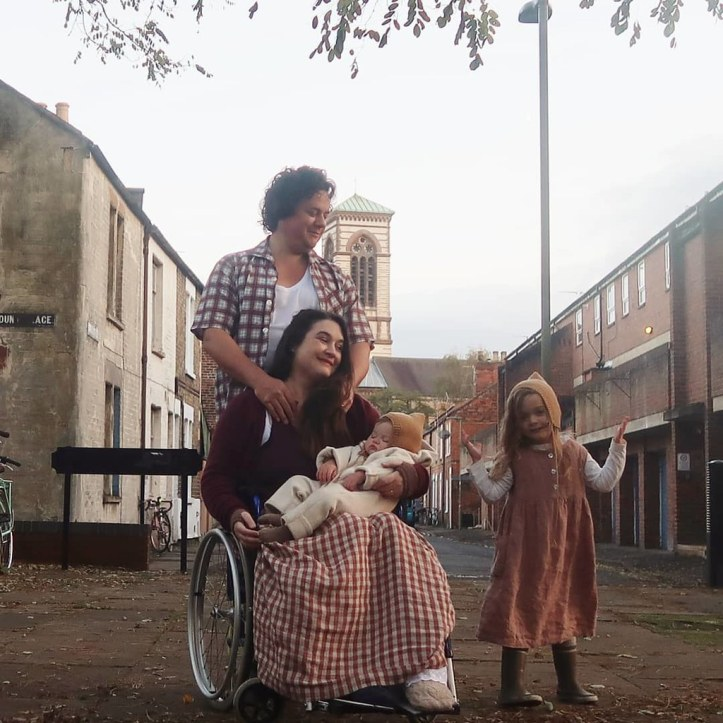 A family photo from 2019 - we're all out near our home in Oxford. Baby Viola is asleep in Lucy's lap, and Lucy is sitting in her wheelchair. Mainie (age 5) is standing to the side, gesticulating (shrugging?) and smiling at the camera. I've just realised you can't actually see that James has one leg. (You think an entire missing limb would show up more frequently on photos to be quite honest.) Viola and Mainie are wearing matching bonnets - which are a triumph IMO. We're all white with varying shades of brown hair.