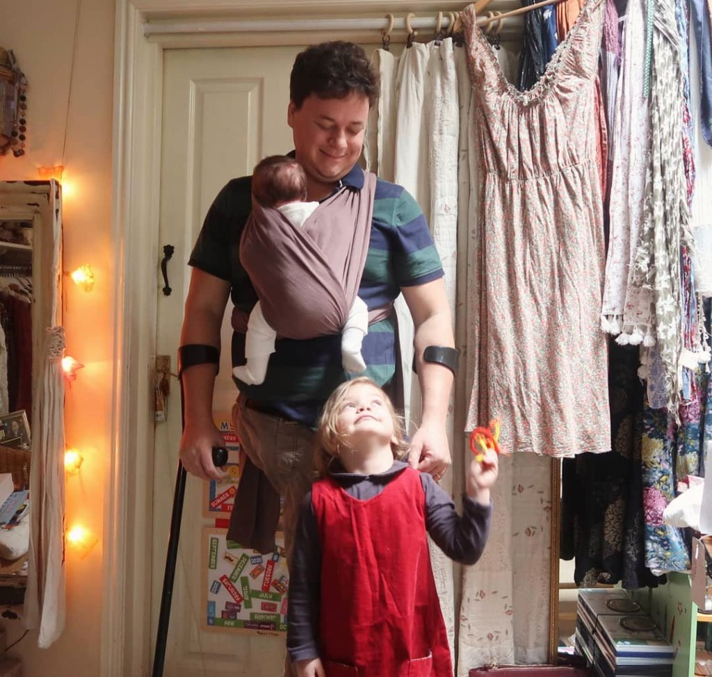 James is standing with newborn Viola strapped to his chest, 4 year old Mainie is looking up at him adoringly.