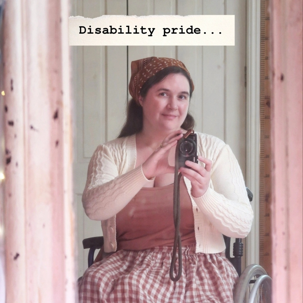 """A mirror selfie. I'm a white woman wearing a brown cotton hair scarf, holding a camera and looking into the lens smiling. The words """"disability pride..."""" are written at the top with a cream torn paper background. The mirror frame is very old and cracked, and is cream, though it looks mysteriously pinkish here."""