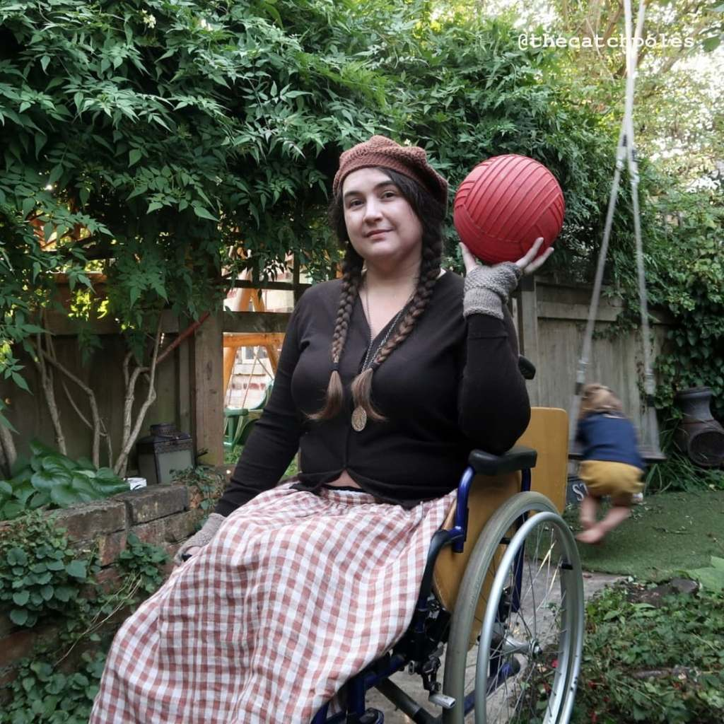 A photo of me, a white woman in her wheelchair holding a ball. I look unconvinced. I have long brown hair in two plaits, am wearing a brown crochet beret and a linen gingham skirt. I'm in my garden. My youngest daughter is on the swing behind me. She is a literal blur.