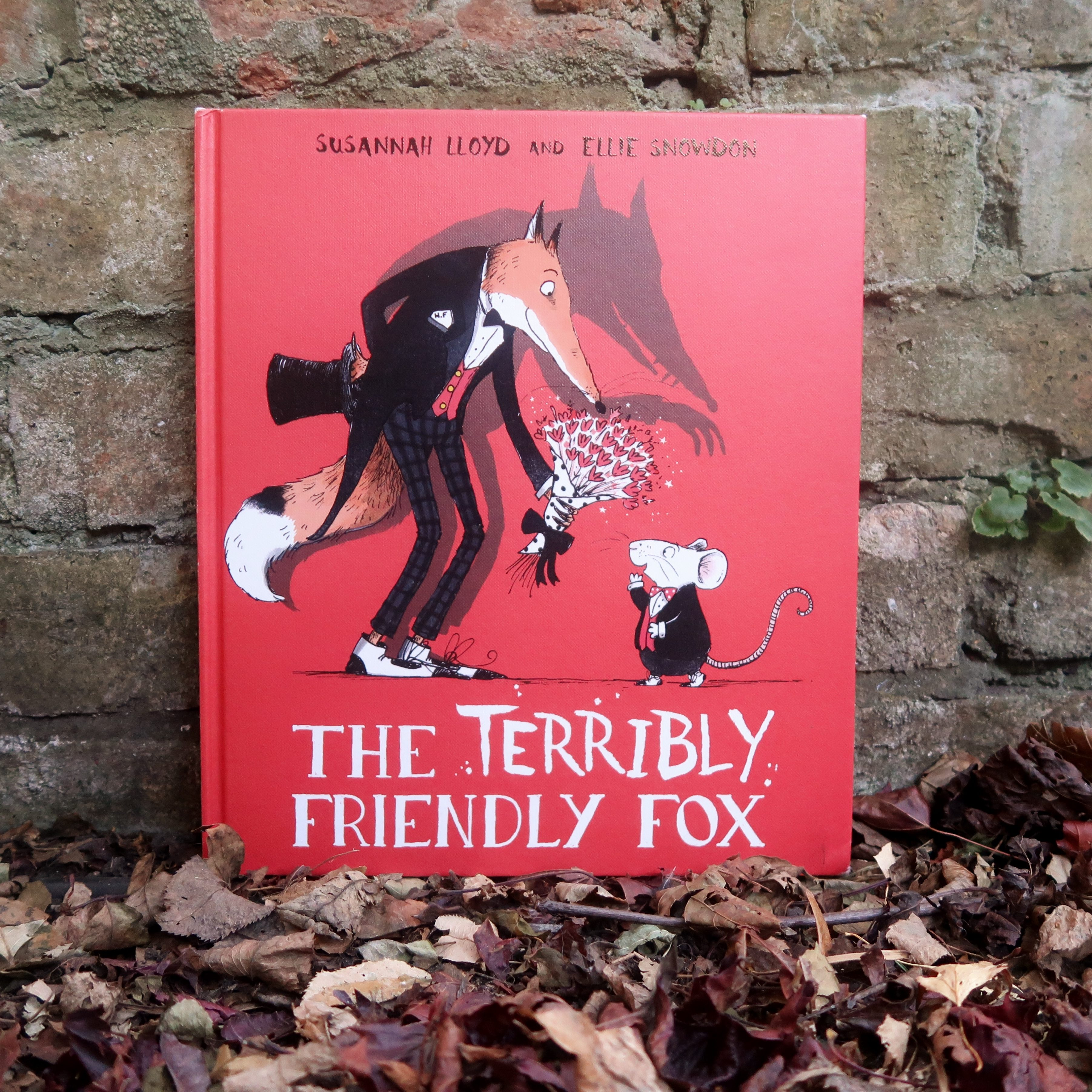 The cover of The Terribly Friendly Fox - a picture book by Susannah Lloyd, illustrated by Ellie Snowden. It's a red hardback, with a besuited fox on the front, presenting a punch of flowers to a small mouse. A shadow looms behind, ominously.