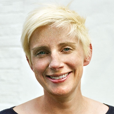 A portrait photo of Emer Stamp, a white woman with short blonde hair. She's smiling at the camera.