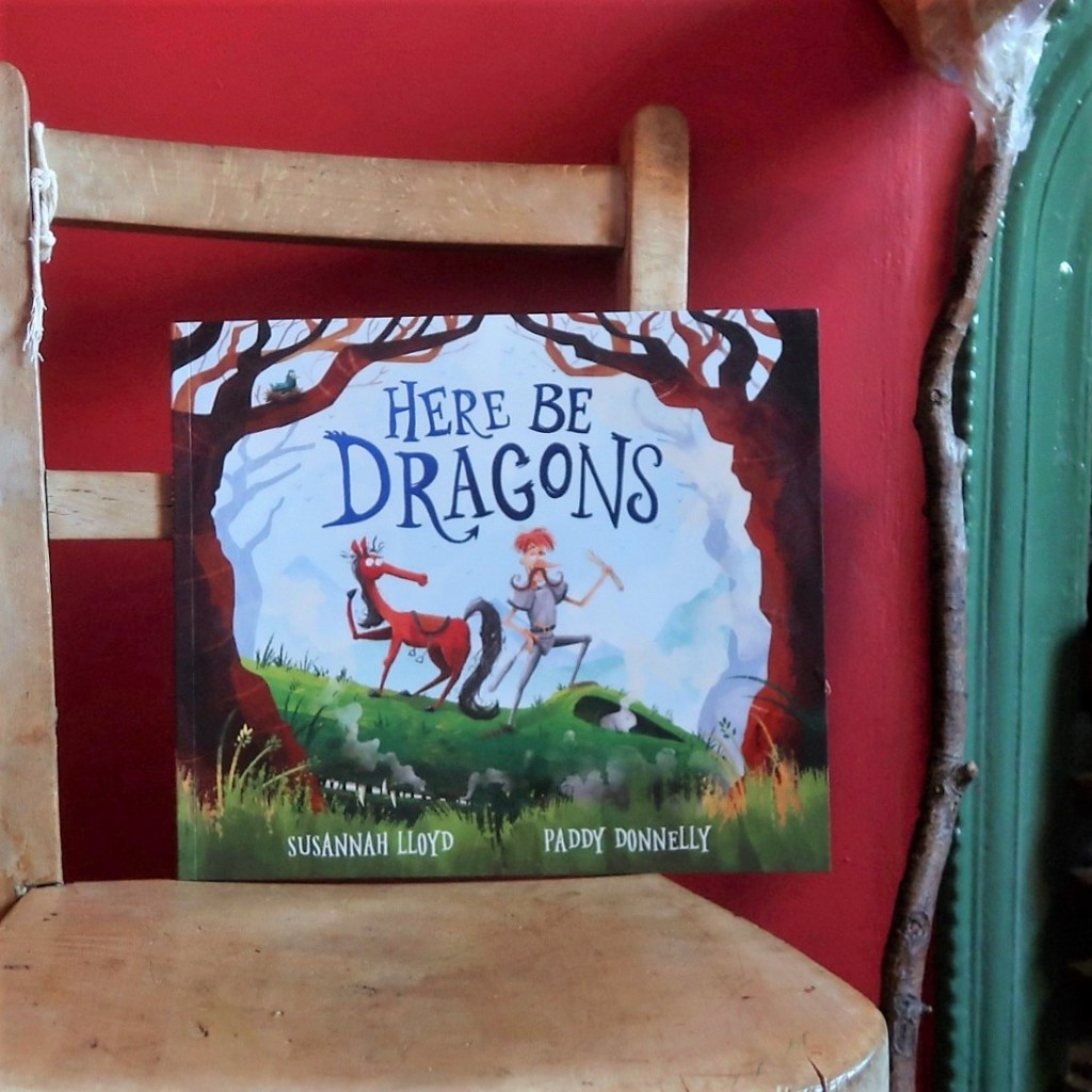 A rounded photo. The cover of Here Be Dragons - another picture book by Susie, illustrated by Paddy Donnelly. A foppish knight with ginger hair stands next to his alarmed horse on the front cover.
