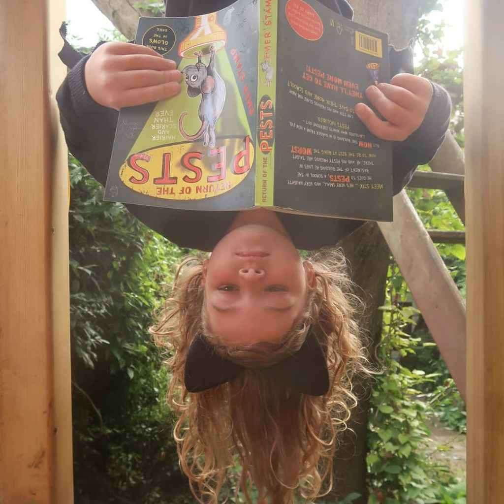 Mainie, a 6yo girl dressed as Batz, a bat, is hanging upside-down reading a copy of Return of the Pests, a middle grade novel. She's white with blondish hair and bat ears (they might be cat ears? Let's go with bat) on a hairband, and is hanging in her treehouse. It looks a bit like her eyes are closed but she is actually reading.