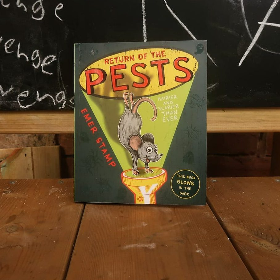 A book portrait of Return of the Pests - it has a black/grey background and a joyful illustrated mouse is doing a handstand in the beam of a torch. The front cover also reads 'Emer Stamp', 'This book glows in the dark', and 'Hairier and scarier than ever'.